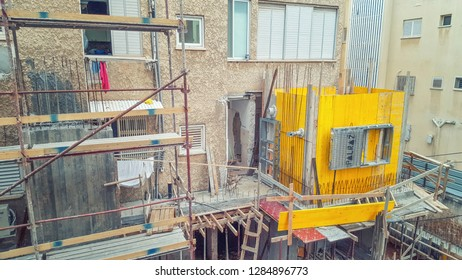 Rishon LeTsiyon, Israel-March 28, 2018: Reinforcement of the old building. Yellow concrete form-work for an additional room with window frame is on the right. A reinforced concrete wall is on the left