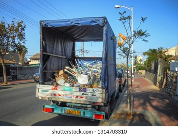 Rishon LeTsiyon, Israel-March 29, 2013: A lorry with a blue canvas tent over the truck body filled with scrap metal junk stands along the pavement in the street.
