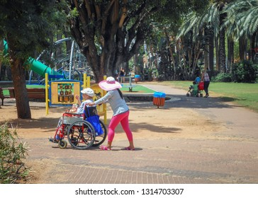 Rishon LeTsiyon, Israel-May 20, 2013: The invalid tender in a pink pants grey shirt and a brimmed hat pushes a wheelchair with a disabled man on the lane of the city park.