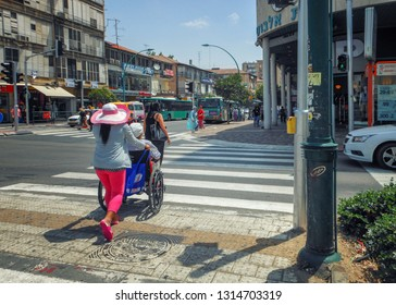 Rishon LeTsiyon, Israel-May 20, 2013: Pedestrians walk across the zebra cross at a green light. Philippine maid in pink pants pushes a wheelchair.