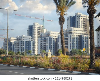 Rishon LeTsiyon, Israel-May 4, 2013: A new living Kiryat Haleom neighborhood towers are under the construction at the background of the separation fence of a multi-lane driveway.