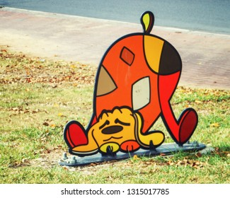 Rishon LeTsiyon, Israel-October 30, 2013: A multi-colored painted metal sculpture of funny dog as an element of the urban landscape. It is set on a green lawn nearby a sidewalk.