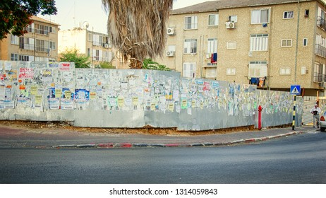 Rishon LeTsiyon, Israel-October 8, 2012: A construction site separated from the sidewalk by a long metal fence covered by layers of different private notices and advertisement.
