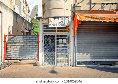 Rishon LeTsiyon, Israel-October 8, 2012: Shoemaker's shop in the sunny street behind the barred gate. There is an ad sign in Russian and Hebrew above the entrance.