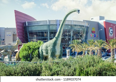 Rishon LeZion, Israel-April 25, 2017: Dinosaurs park. Long green neck of Brachiosaurus rises suddenly among the palms and bushes nearby of round two story glass entrance to the Cinema city building.