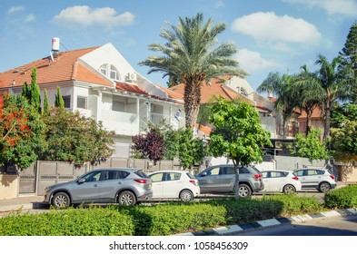 Rishon LeZion, Israel-June 10, 2017: Typical white two-floor townhomes with a red tiled roof with a penthouse in the living neighborhood located at Ha-Shakhar Street.