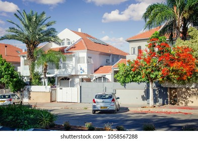 Rishon LeZion, Israel-June 10, 2017:  Two-story private white walls house with attic under red tiles sloped roof. The medium shot was taken on a sunny summer day at Ha-Shakhar Street.