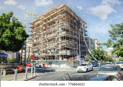 Rishon LeZion, Israel-June 10, 2017: Scaffolding around 4-storey house is located at 35 Katznelson Street. The building is being renewed in accordance with Tama 38 program. White clouds on blue sky
