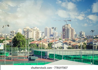 Rishon LeZion, Israel-June 17, 2017: View of district Katsanelson. There are both types of houses small with tiled roofs and  tall condominiums. Big outdoor tennis courts are located in the foreground