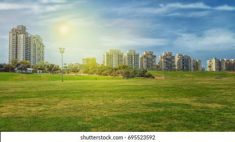 Rishon LeZion, Israel-March 19, 2016: View of big green field in front of Kiryat Rishon district under beautiful sky. There are some multi story condominiums in the background. Horizontal shot