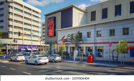 Rishon LeZion, Israel-September 10, 2017:  Israeli Post Office 3 story building located at Rothschild St.57. Big plasma panel screen of Castro shop is on the wall. Some cars stand at a traffic light.