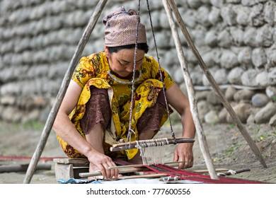 RISHTAN, UZBEKISTAN - MAY 16, 2017: Uzbek woman in traditional clothes weaves using an old loom, in Rishtan, Uzbekistan.