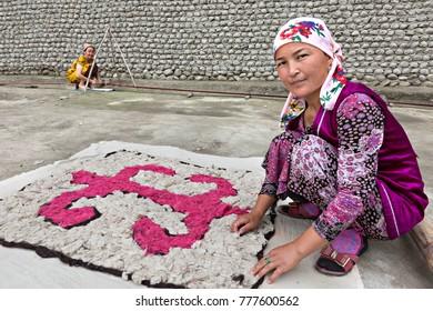 RISHTAN, UZBEKISTAN - MAY 16, 2017: Uzbek woman in local costumes makes felt, in Rishtan, Uzbekistan.
