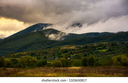 rising clouds in mountainous countryside at menacing sunrise. village at the foot of the mountain. rainy weather