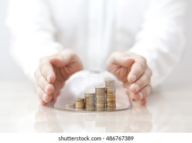 Rising coins protected under a glass dome and hands