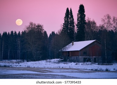 Rising full moon and countryside scenery with old barn and snow on the field. Very calm and peaceful atmosphere of cold night in winter.