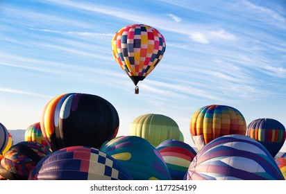 A rising hot-air balloon while others are still on the ground, competition concept. leading. leadership. Concept of The First Place. First balloon rising above others.