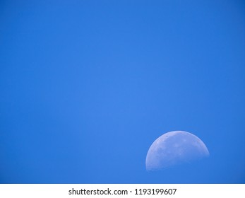 A rising moon in the blue morning sky over Thailand.