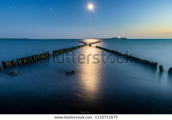 Rising moon over the wooden Breakwaters in Dranske, Ruegen, Germany
