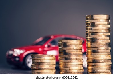 Rising piles of coins and a red car in the background