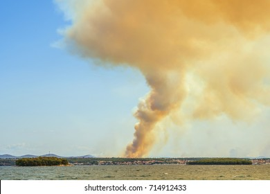 rising smoke from forest fire behind city Biograd on the sea at Croatian coast