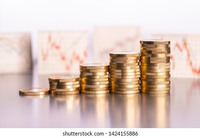 Rising stacks of coins and charts with stock prices in the background