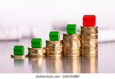 Rising stacks of coins, four green cottages and a red house