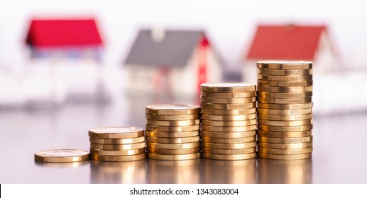 Rising stacks of coins with houses in the background