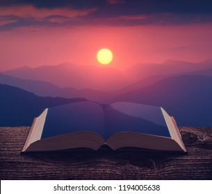 Rising of the sun above the blue mountains on the pages of an open magical book. Majestic landscape. Nature and education concept.