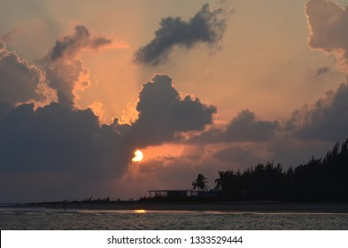 The rising sun can just be seen through some clouds, which range from dark grey to pale pink. Below is a wooden shack surrounded by trees beside a beach on a tropical island.
