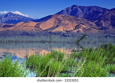 The rising sun illuminates hills and mountains beyond the upper end of Lake Isabella in California
