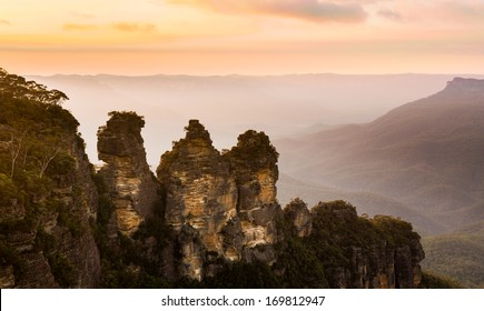 Rising sun illuminates the Three Sisters rock formation in the valley from Echo Point overlooking the majestic Blue Mountains near Sydney NSW Australia