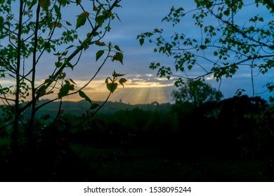 Rising sun lights up landscape through gap in clouds silhouetting forground trees.