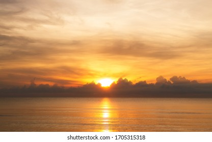 The rising sun over clouds in the sea. The morning light with a beautiful orange sky.