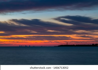 The rising sun paint the sky with vivid colors over Florida's San Carlos Bay with tall buildings of Fort Myers Beach and the Ybel Lighthouse on Sanibel Island silhouetted on the horizon.