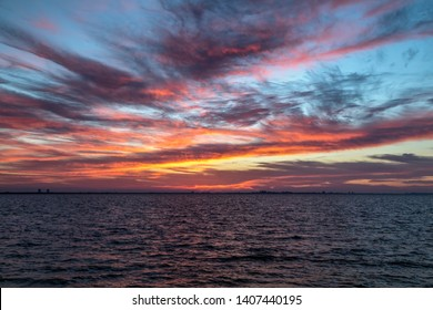 The rising sun paints a cloudy morning sky with vivid colors over San Carlos Bay with Fort Myers Beach, Florida on the horizon