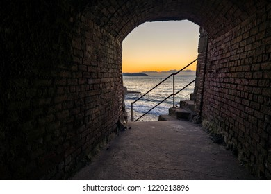 The rising sun peeps through a small stretch of tunnel in Charlestown, Cornwall. This tunnel would have been a crucial part of the harbours once bustling China Clay export trade.