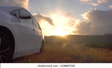 Rising sun reflects on the side of parked vehicle in a national park. Car travel