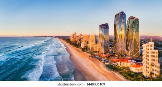 Rising sun shining on modern urban towers of Surfers paradise in Australian Gold Coast facing endless waves of Pacific ocean - aerial panoramic view.