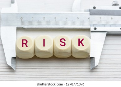 Risk assessment / risk analysis and management concept : Words RISK on wood blocks and a vernier caliper with scales, depict evaluation for financial risk of an investor involved in stock, bond market