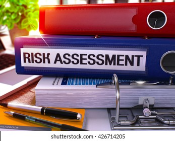 Risk Assessment - Blue Office Folder on Background of Working Table with Stationery and Laptop. Risk Assessment Business Concept on Blurred Background. Risk Assessment Toned Image. 3D.