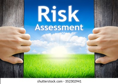 Risk Assessment . Hand opening an old wooden door and found Risk Assessment word floating over green field and bright blue Sky Sunrise.