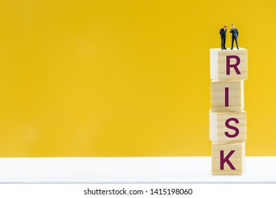 Risk assessment and risk tolerance, financial concept : Miniature figurine businessmen CEO, CFO talk / negotiate on a company / firm to manage risk. Two top leaders stand on wood cubes with word RISK