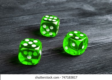 risk concept - playing dice at black wooden background. Playing a game with dice. Green casino dice rolls. Rolling the dice concept for business risk, chance, good luck or gambling