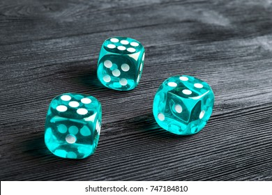 risk concept - playing dice at black wooden background. Playing a game with dice. Blue casino dice rolls. Rolling the dice concept for business risk, chance, good luck or gambling