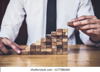Risk To Make Business Growth Concept With Wooden Blocks, hand of man has piling up and stacking a wooden block, Alternative risk concept, plan and strategy in business.
