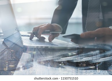 Risk management, business investment concept. Trader, businessman using mobile phone working, monitoring on stock exchange report on laptop computer with financial background and the city.