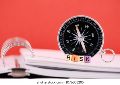 Risk management concept.Risk word cube on book over compass and red background