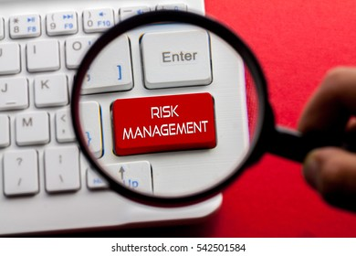 Risk Management word written on keyboard view with magnifier glass