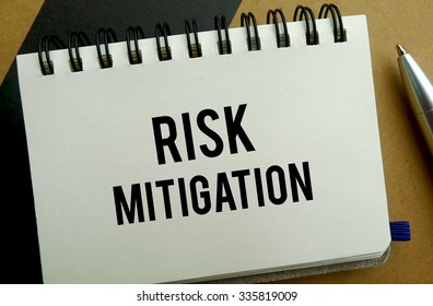 Risk mitigation memo written on a notebook with pen